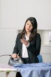 Gebohrte unglückliche Hausfrau, die das Bügeln tut Lizenzfreies Stockfoto