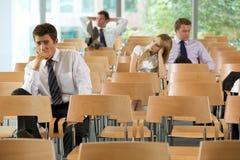 gebohrte Unternehmensleiter, die im Konferenzsaal sitzen Lizenzfreie Stockfotos