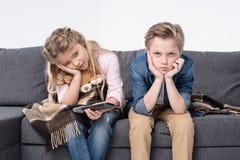 Gebohrter Bruder und Schwester, die auf Sofa sitzt und Fernbedienung hält Stockbild