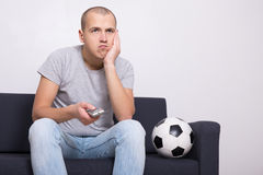 Gebohrter Fußballfan mit aufpassendem Spiel des Balls im Fernsehen Lizenzfreie Stockfotografie