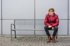 Gebohrter jugendlich Junge, der die Gesichter ausdrücken das negative Gedankensitzen macht Lizenzfreie Stockfotografie