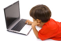 Gebohrter Junge, der Laptop verwendet Stockfotos
