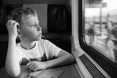 Gebohrter Junge mit Süßigkeitsblick im Zugfenster Stockfotografie