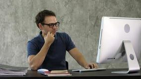 Gebohrter junger Mann am Schreibtisch vor Computer stockfotografie
