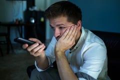 Gebohrter kaukasischer Mann, der fernsieht und auf einer Couch oder Hotel zu Hause sitzen zapping Lizenzfreie Stockfotos