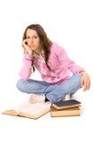 Gebohrter Kursteilnehmer, der auf dem Fußboden mit Büchern sitzt Stockfotografie