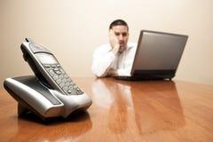 Gebohrter Mann, der am Laptop sitzt Stockfoto