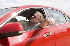 Gebohrter Mann im roten Auto Stockfotografie