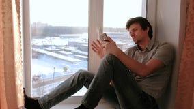 Gebohrter Mann passt etwas im Internet in seinem Mobile beim Sitzen auf einem Fensterbrett auf stock footage