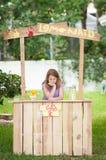 Gebohrtes junges Mädchen ohne Kunden auf ihrem Limonadestand Stockfotos
