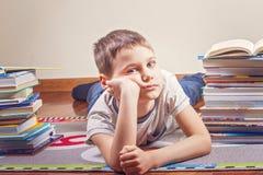 Gebohrtes Kind, das zwischen Stapel von Büchern liegt stockfoto