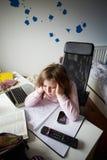Gebohrtes Mädchen im Schlafzimmer unter Verwendung des Laptops Stockbilder