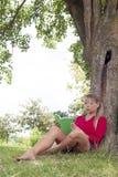 Gebohrtes Mädchen 20s, das ein Sommerbuch unter einem Baum liest Stockbilder