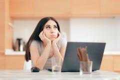 Gebohrtes müdes Mädchen, das vom Haus auf ihrem Laptop arbeitet lizenzfreie stockfotografie