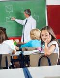 Gebohrtes Schulmädchen, das im Klassenzimmer sitzt Stockbild