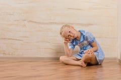 Gebohrtes sitzendes Aufpassen des kleinen Mädchens und Aufwartung Lizenzfreies Stockbild