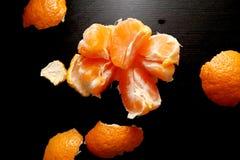 Geborstelde mandarijn op een zwarte achtergrond Nuttige citrusvrucht royalty-vrije stock afbeelding