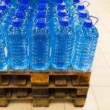 Gebotteld nog water op het palet Stock Fotografie
