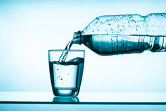 Gebotteld water en een glas Royalty-vrije Stock Afbeelding