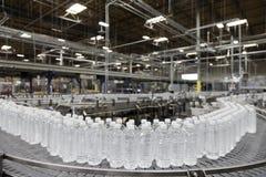 Gebotteld water op transportband bij bottelarij Stock Afbeeldingen