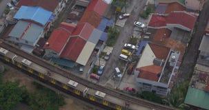 Gebouwen en spoorweg met een voorbijgaande trein in stad van Kuala Lumpur, Maleisië stock footage