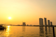 Gebouwen op Chaophraya-rivieroever in avond Stock Afbeeldingen