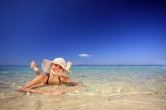 Gebräunte blonde Frau im Bikini im Meer Stockbilder