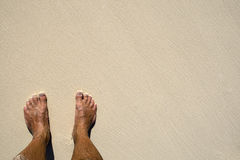 Gebräunte Fahrwerkbeine auf Sandstrand Stockbilder