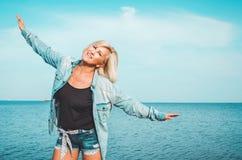 Gebräunte gesunde mittlere Greisin mit der Denimkleidung, die Spaß hat Active, genießen Konzept am sonnigen Sommertag, draußen Stockfotografie