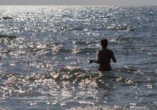 Gebräunte schulterfreie Frau, die geht, im glänzenden Meer zu schwimmen Stockbild