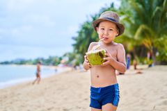 Gebräunter asiatischer Junge steht auf dem Strand in einem Hut und in einer Getränkkokosnuß stockfotografie