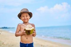 Gebräunter asiatischer Junge steht auf dem Strand in einem Hut und in einer Getränkkokosnuß lizenzfreie stockbilder