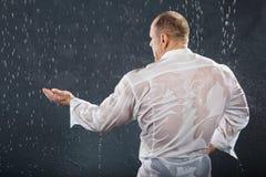 Gebräunter Bodybuilder steht im Regen Stockfotos