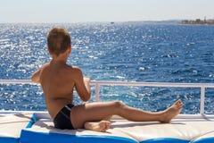 Gebräunter Junge, der zum blauen Meer vom Yachtbrett schaut Lizenzfreie Stockfotos