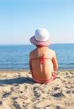 Gebräuntes Mädchen, das auf dem Strand im weißen Hut sitzt Stockfoto
