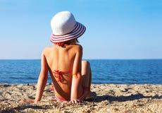 Gebräuntes Mädchen, das auf dem Strand sitzt Stockbild