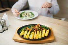 Gebraden aardappel met paddestoelencantharel prachtig plattelander in een zwarte plaatplattelander op een houten lijst stock fotografie