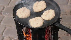 Gebraden aardappelpannekoeken, gefrituurd in een pan over een open brand stock footage