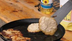 Gebraden aardappelpannekoeken, gefrituurd in een pan over een open brand stock videobeelden