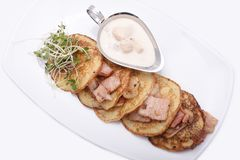 Gebraden aardappelpannekoeken met bacon en paddestoelsaus stock foto
