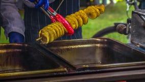 Gebraden aardappels in de vorm van spiraal op houten stok De aardappels braadden tot de gouden kleur op metaaldienblad tijdens pi royalty-vrije stock fotografie