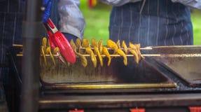 Gebraden aardappels in de vorm van spiraal op houten stok De aardappels braadden tot de gouden kleur op metaaldienblad tijdens pi stock fotografie
