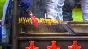 Gebraden aardappels in de vorm van spiraal op houten stok De aardappels braadden tot de gouden kleur op metaaldienblad tijdens pi stock foto's