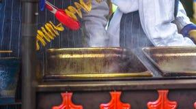 Gebraden aardappels in de vorm van spiraal op houten stok De aardappels braadden tot de gouden kleur op metaaldienblad tijdens pi stock afbeelding