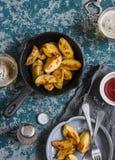 Gebraden aardappels in een gietijzerpan en twee glazen bier op houten achtergrond Royalty-vrije Stock Foto's