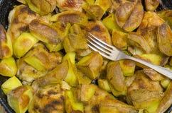 Gebraden aardappels met kippendijen en een vork die op bovenkant liggen Stock Afbeelding