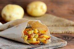 Gebraden aardappels met kruiden Eigengemaakte gebraden aardappels in document en op een houten lijst Het recept van de aardappels Stock Afbeeldingen