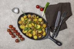 Gebraden aardappels met paddestoelen en ui in ijzerpan bij grijze achtergrond stock afbeelding