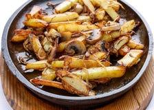 Gebraden aardappels met uien en paddestoelen stock afbeelding