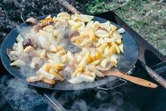 Gebraden aardappels met vlees en worsten die concept het koken op een open brand roosteren Picknick in het weekend Stock Foto's